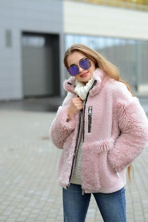 girl in pink coat posing in the city