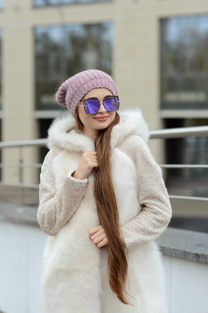 girl in down jacket with fur posing in the city on the background of glass houses