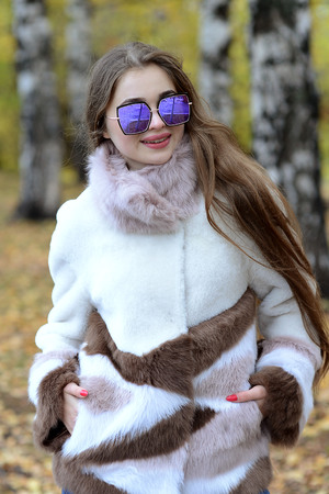 girl in a coat and sunglasses walking in the woods