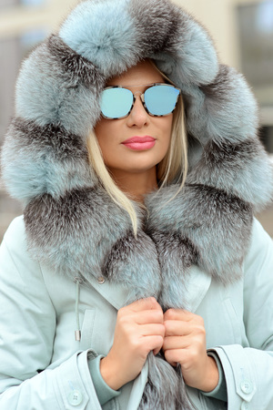 portrait of a girl in a down jacket with fur in blue glasses