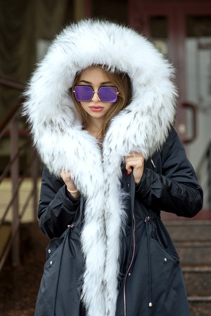 a girl in a black jacket with a white fur collar and glasses posing on the street