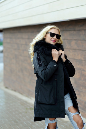 girl in black down jacket and black glasses posing on the street