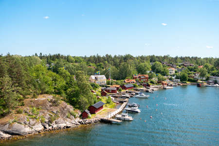 Cozy Scandinavian cottages located on the coastline of the archipelago in Sweden. Colorful summer landscape with houses on the shore of the Baltic Sea.
