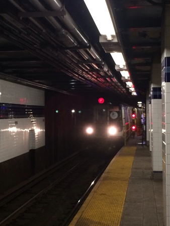 Inside NYC subway station as front of train pulls into the station