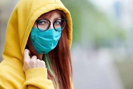 a young girl with glasses, a reusable medical mask, and a yellow hood turns and looks around