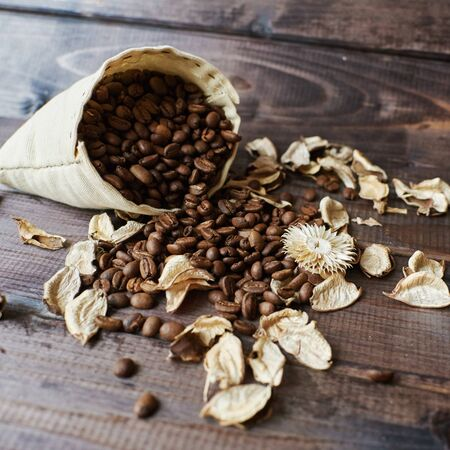 A bag of scattered roasted coffee beans on a brown wooden background