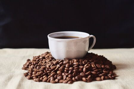 A Cup of espresso coffee drink on a handful of roasted brown coffee beans