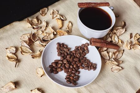 Brown coffee grains on a saucer in the shape of a star next to the Cup of espresso
