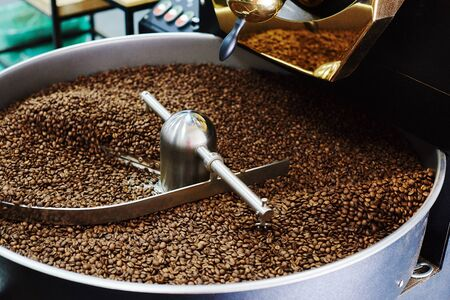 Coffee brown roasted beans. The roasting process in the roaster
