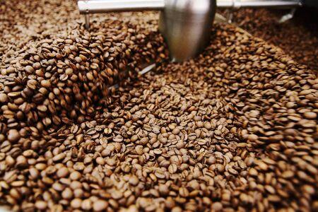 Grains de café torréfiés bruns. Le processus de torréfaction dans le torréfacteur Banque d'images