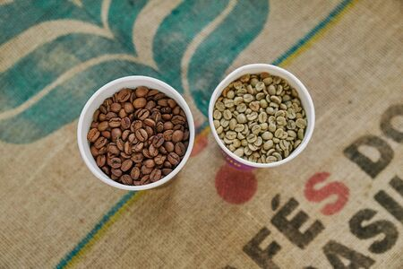 Coffee beans before and after roasting. Top view of brown and green grains