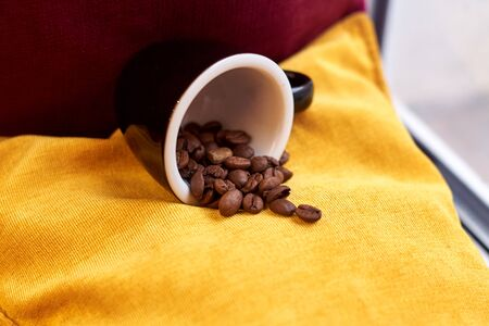 Coffee roasted brown beans in a white Cup on a yellow background Фото со стока
