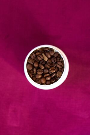 Coffee roasted brown beans in a white Cup on a purple background