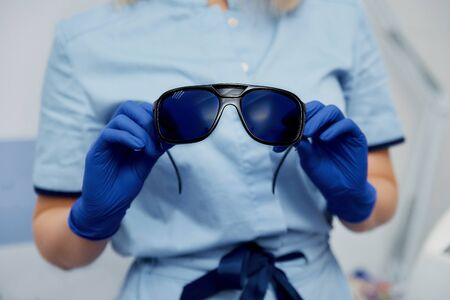 blue glasses to protect your eyes from laser radiation in the hands of a cosmetologist in blue gloves