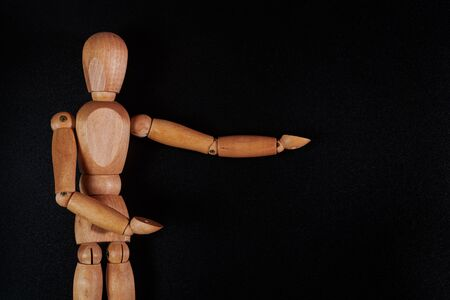 a wooden model of a man on a black background shows his wooden hands to the side. A puppet with wooden hands points to the side