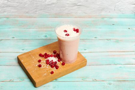 cold pink milkshake on coconut milk with coconut shavings and red currant berries. Summer drink in still life in a transparent plastic glass on a light blue wooden background