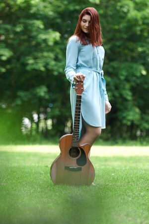 a girl with a guitar stands in an open green area. a full-length girl with a guitar is on the lawn in nature