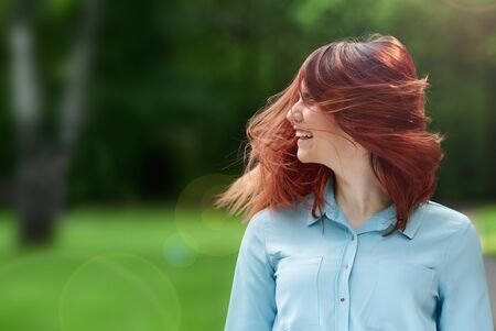 the girl smiles widely, shakes her head with red hair and is happy on the green natural background. happy young bright girl laughing on the summer lawn