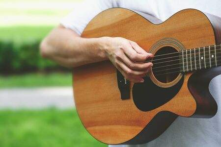 close-up of a brown classical acoustic guitar with a male musician's hand playing the strings. Stringed musical instrument in the hands of a person close up on a blurred natural background 写真素材
