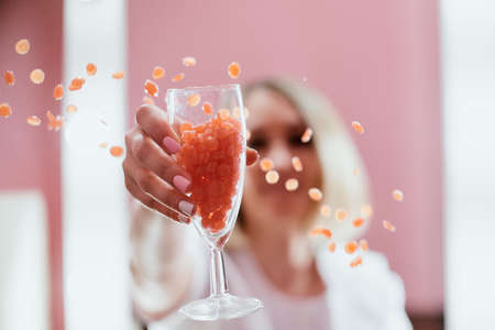 a girl in full focus holds a transparent glass of champagne, from which wax in the form of granules for depilation of pink color is scattered Banque d'images