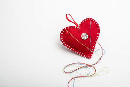 Heart shaped pincushion with a needle and thread.