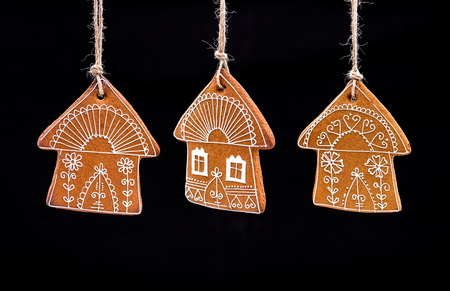 Home-baked and decorated gingerbread on black background. Gingerbread Christmas. Stock Photo