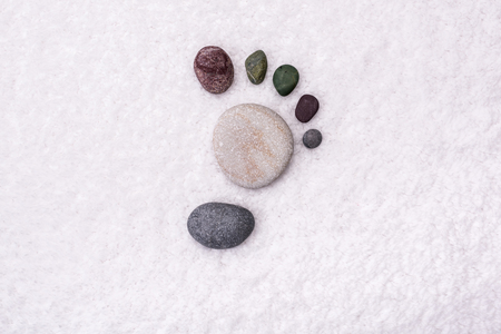 toweling: The footprint is made up of stones on a white towel, soft background.
