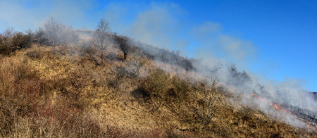 Farmers burn the grass on the hill early spring, another cause of global warming. Smoke pollution.