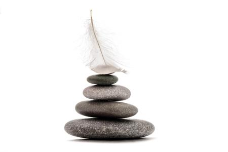 Meditation stones and plume isolated on white background. Stock fotó