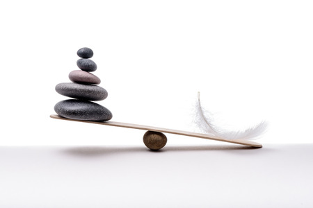 Stone balance with plume. Concept of heavy and light. Reklamní fotografie - 95715975