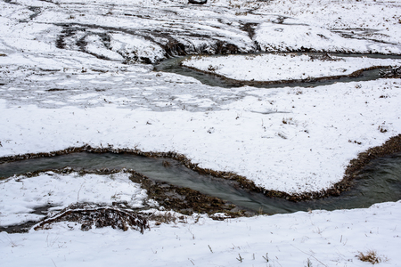 Spring melting of ice, spring thaw. Spring creek flowing in the field with melting snow.