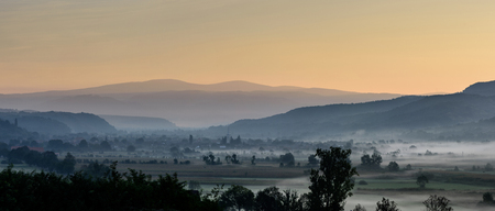 Breathtaking morning lansdcape of a small transylvanian village covered in fog. Autumn morning. Stock fotó