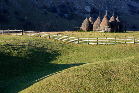 Autumn landscape in the mountains with stack of hay. Traditional hay stacks, typical rural scene of Romania.