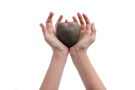 Hand of a girl holding a heart made out of clay. Conceptual image with hands and heart. Making a heart shape isolated on a white background. Stock fotó - 117960532