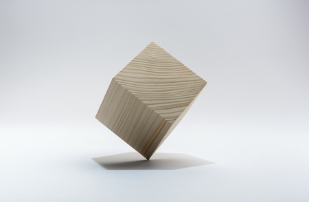 Wooden cube on corner, on gray background.
