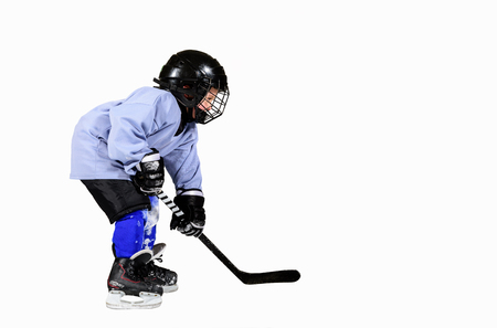 Little hockey player in full equipment, isolated on white background and copy space for text.