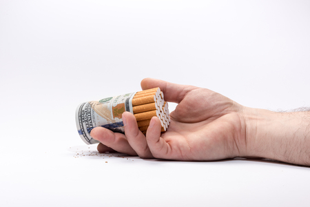 Smoking kills. Cigarettes wrapped in hundred dollars banknote in human hand.