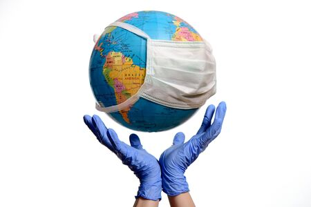 Earth globe with a protective mask and hands, isolated on a white background. Human Epidemic Danger.