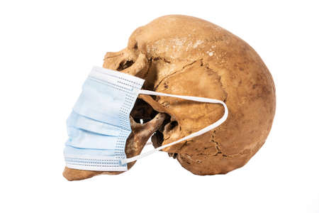 Human skull with medical mask isolated on white background.