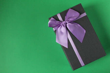 new year \ 's Christmas holiday mother \' s day Valentine \ 's day birthday anniversary gift box black with purple purple fuchsia colors with a bow on a green background copy space