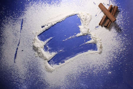 background meal flour or powdered sugar on a blue bright background with a place of copy space. Archivio Fotografico