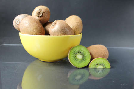 still life of kiwi fruit in a yellow bowl plate and pieces of mug next to on a black background with a reflection copyspace