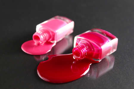 Beauty background two bottles of nail polish bottles red or burgundy pink spill poured on the table on a black background with a copyspace.
