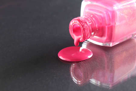 Pink nail polish is poured out of the bottle bottle on a black background with a copyspace place for text.