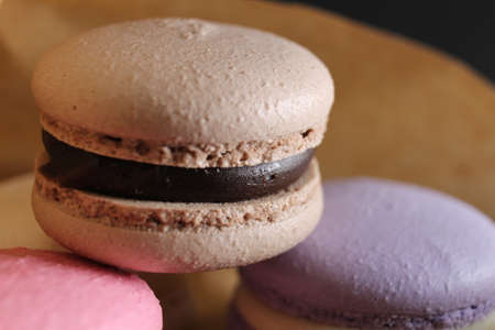 Three multi-colored macaroons on crafted brown paper next to lie sticks cinnamon on a black background with place for text and with a copyspace.