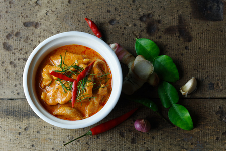 Panaeng Curry with Pork in porcelain bowl on wood background ,famous thai food