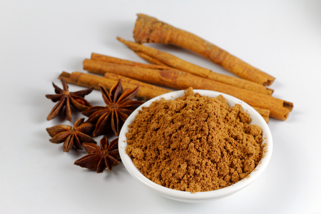 Chinese Five-Spice powder in a bowl with cinnamon and star anise on white paper 免版税图像
