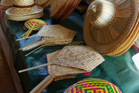 weaving bamboo fan and hat sell in traditional market Thailand Reklamní fotografie
