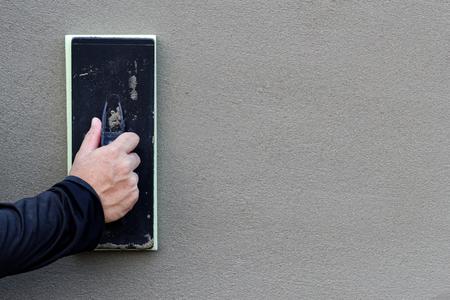 Betonnen muur achtergrond, Hand met behulp van plastic spons troffel pleisterwerk om cement muur af te werken