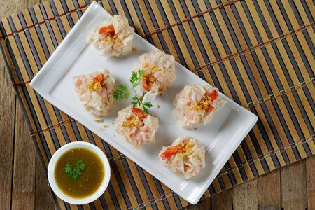 steamed shrimp wontons on white plate with sauce Stock Photo